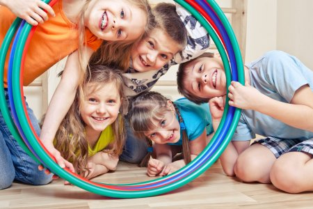 Photo for Five cheerful kids looking through hula hoops - Royalty Free Image