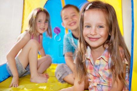 Three kids inside an outdoor camping tent