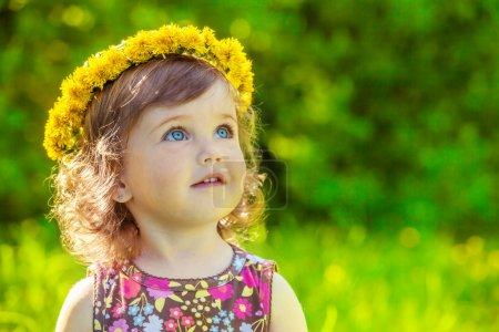Photo for Portrait of a preschool girl with yellow flowers headwreath on - Royalty Free Image