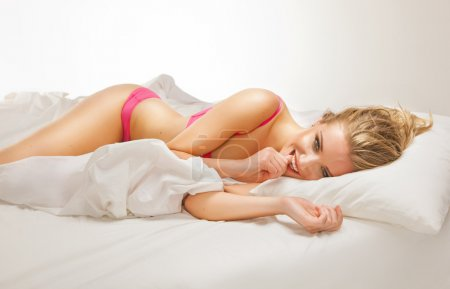 Photo for Smiling woman lying on bed - Royalty Free Image