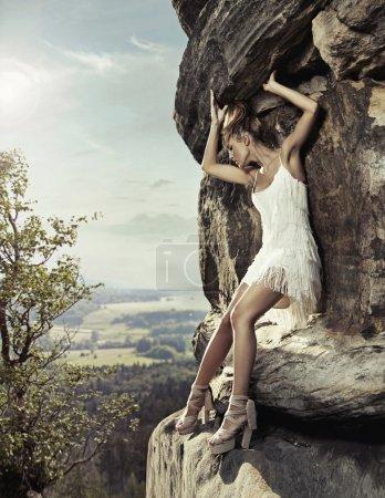 Blonde beauty posing on a dangerous rock