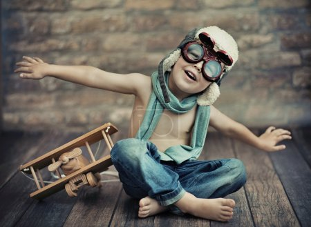 Foto de Small boy playing with a plane, on wooden floor - Imagen libre de derechos