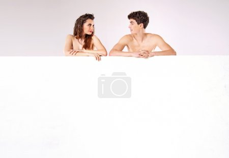 Attractive nude couple behind the board