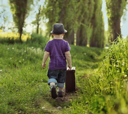 Photo for Little kid carrying a suitcase - Royalty Free Image
