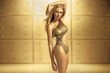 Photo for Aluring female model in golden swimsuit - Royalty Free Image