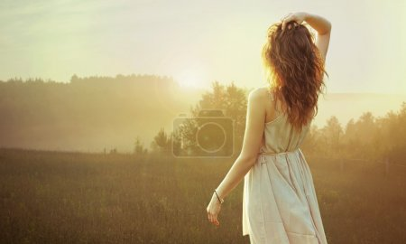 Photo for Pretty brunette lady watching the sunset - Royalty Free Image