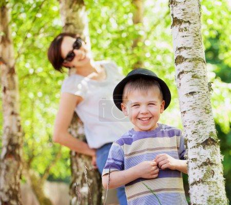 Foto de Niño sonriente y su mamá muy en el fondo - Imagen libre de derechos