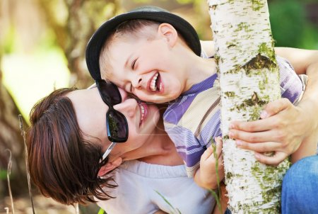 Photo for Laughing small boy hugged by his pretty mother - Royalty Free Image