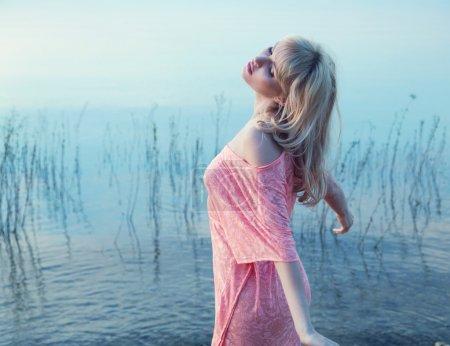 Photo for Sensual blonde lady enjoying cold lake water - Royalty Free Image