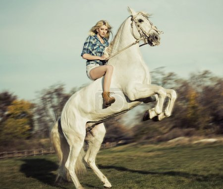 Serious blonde woman riding the horse