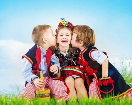 Photo pour Trois enfants joyeux portant des costumes nationaux - image libre de droit