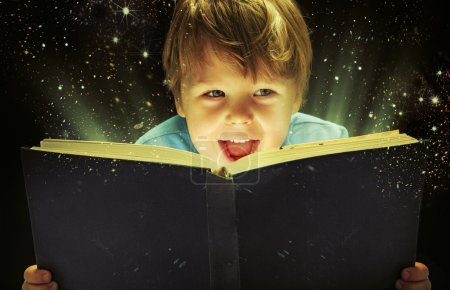 Small boy carrying a magic book