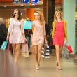 Three self-cofident female friends on the shopping...
