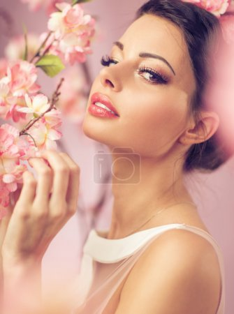 Photo for Brunette beautie with the pink flowers - Royalty Free Image