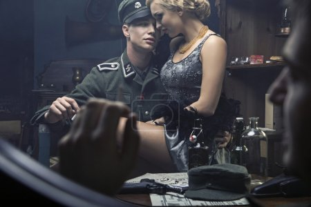 Handsome german soldier with blonde woman on his knees