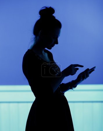 Silhouette  of woman playing the cell phone