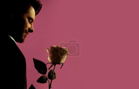 Photo pour Gestionnaire beau détendu tenant la fleur - image libre de droit