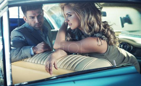 Relaxed young couple in the retro car