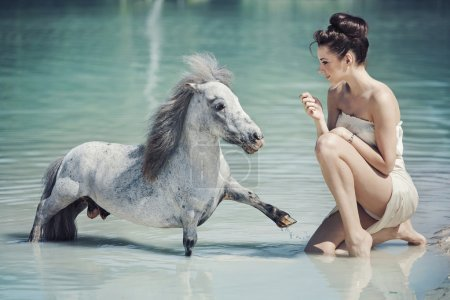 Photo pour Alluring lady playing with the pony in the pool - image libre de droit