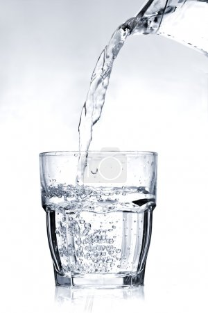 Filling a glass with water on a light blue background