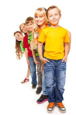 Foto de Cinco feliz 8 años chicos y chicas aislado sobre fondo blanco y parados juntos uno tras otro - Imagen libre de derechos