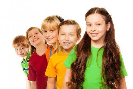 Foto de Cinco niños felices en una línea cada uno detrás de otro, con sonrisa natural y chica con pelos largos y oscuros en el frente - Imagen libre de derechos