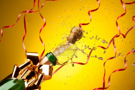Photo for Popping cork from Champaign bottle with gold bow and ribbons on background, with splashes all around the yellow background - Royalty Free Image