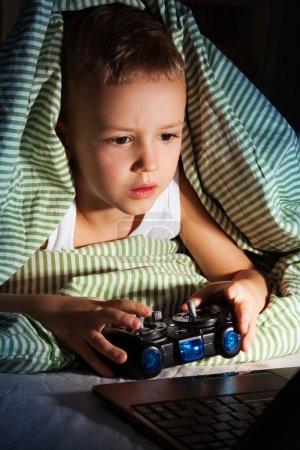 Foto de Poco cinco años viejo juegos de ordenador con consola de videojuegos - Imagen libre de derechos