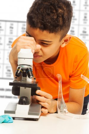Photo for Black boy in orange looking in microscope on biology lesson - Royalty Free Image