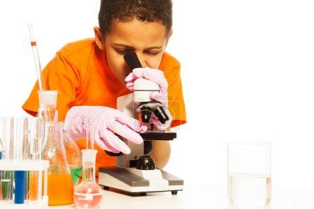 Cute black boy looking into microscope
