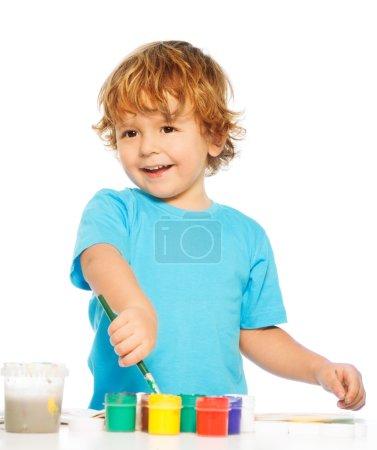 Photo pour Peinture garçon heureux de deux ans avec pinceau et couleurs - image libre de droit