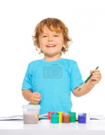 Photo for Happy smiling kid painting with paintbrush and colorful vivid colors, smiling, isolated - Royalty Free Image