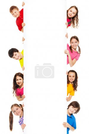 Foto de Seis niños, muchachos y muchachas mostrando pizarra en blanco para hacer publicidad a insertarse, aislado en blanco - Imagen libre de derechos