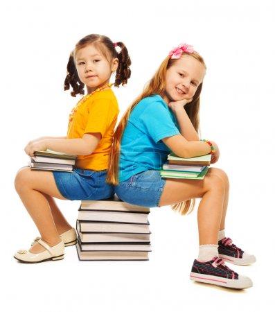 Foto de Dos felices pequeño 6 o 7 años de edad las niñas asiáticas y caucásicas sentado en libros de pila en su mano y sonriendo pie aislado en blanco - Imagen libre de derechos