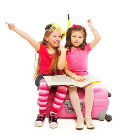 Foto de Dos 6-7 años de edad salió muy chicas sentadas en maleta con mapa preparándose para viajar hacia las manos, con snorkel y máscara, aislado en blanco - Imagen libre de derechos