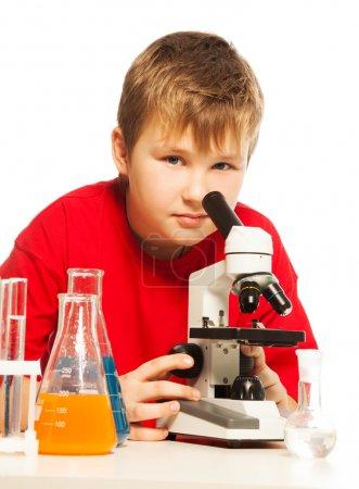 Photo pour Mignon caucasien garçon dans laboratoire avec microscope et test laboratoire equipmen - image libre de droit
