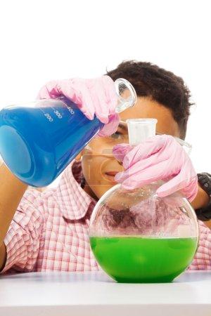 Photo pour Noir 10 ans garçon mélange de produits chimiques avec deux grandes fioles - image libre de droit