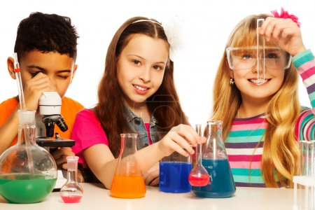 Photo for Three kids, two girls blond and brunet with test tubes and flasks conducting experiments and black boy with microscope, isolated on white - Royalty Free Image