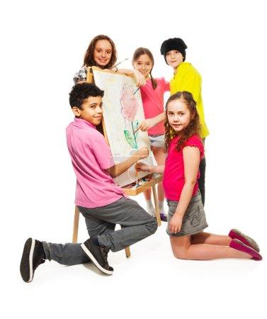 Photo pour Groupe de quatre enfants heureux, garçons et filles peignant avec des pinceaux sur la toile blanche - image libre de droit