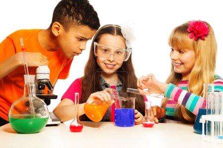 Photo pour Trois enfants, deux filles blondes et brunettes et un garçon noir, avec microscope, éprouvettes et flacons conduisant des expériences, isolés sur du blanc - image libre de droit