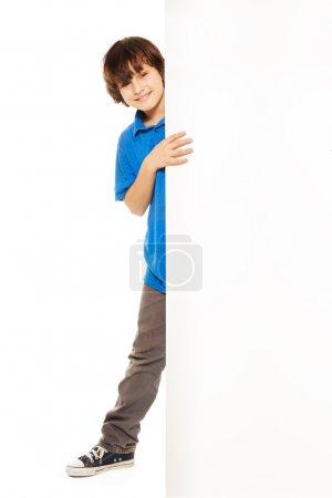 Happy boy looking from blank billboard