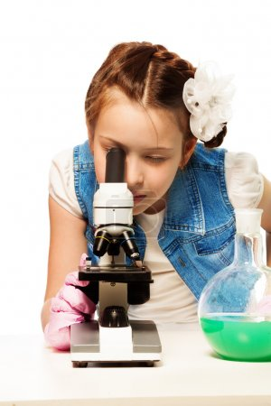 Photo for Girl researching looking into microscope with lab tubes - Royalty Free Image