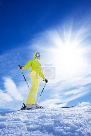 Photo pour Heureuse jeune femme skieuse debout sur le sommet de la montagne par une journée ensoleillée - image libre de droit
