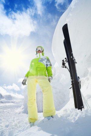 Photo pour Jeune skieuse heureuse debout avec ski mis dans la neige énorme neige haute dérive et montagne sur fond - image libre de droit