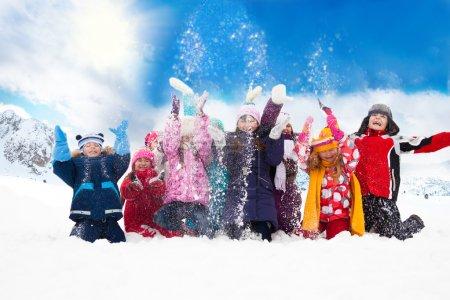 Photo pour Grand groupe de diversité à la recherche de jeunes garçons et filles jeter la neige dans l'air ensemble - image libre de droit