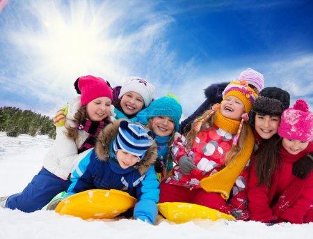 Photo pour Grand groupe d'enfants jouant ensemble dans la neige par une journée ensoleillée - image libre de droit