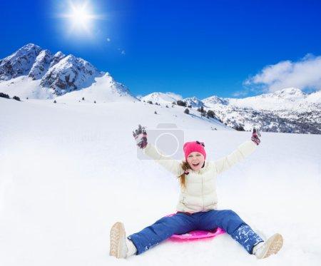 Photo pour Joyeux fille assise sur luge avec ses mains levées, portant un masque de ski, dans les montagnes le jour ensoleillé - image libre de droit