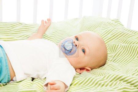 Photo pour Calmer le petit garçon de 6 mois, couché dans son berceau avec sucette - image libre de droit