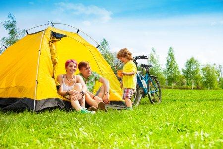 Photo pour Jeune couple avec enfant assis dans la tente lors d'une randonnée à vélo - image libre de droit