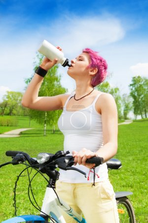 Photo for Young woman with red hairstyle sitting on a bike and drinking water in a bottle - Royalty Free Image